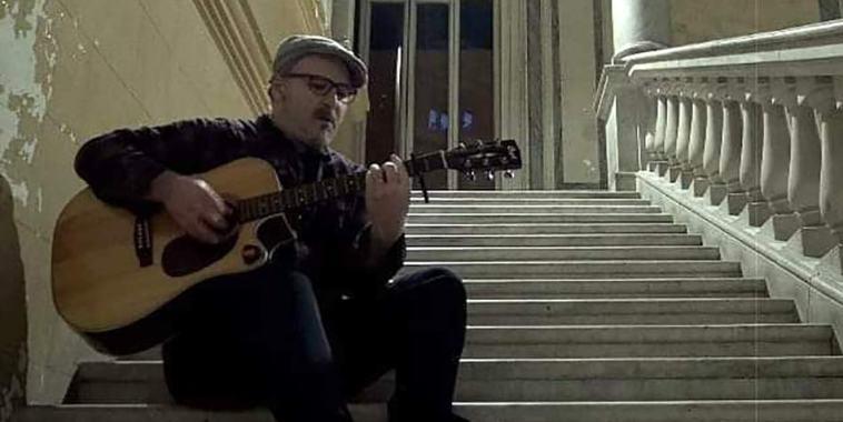 Il cantautore Clemente suona seduto su una scala