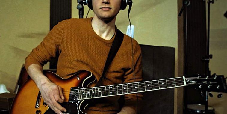 Yuri Crescenzio con la chitarra e maglioncino arancione