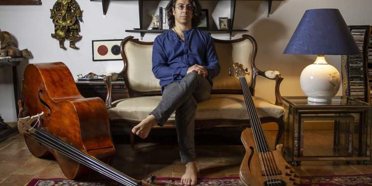 Filippo Macchiarelli seduto su un divano con basso e contrabbasso