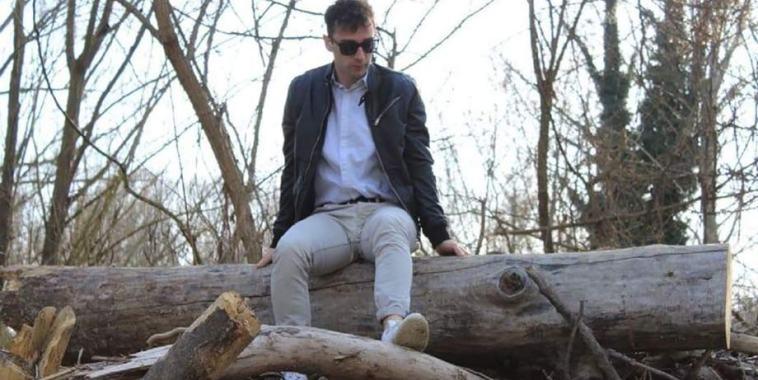 Il rapper KAALI seduto su un tronco di albero
