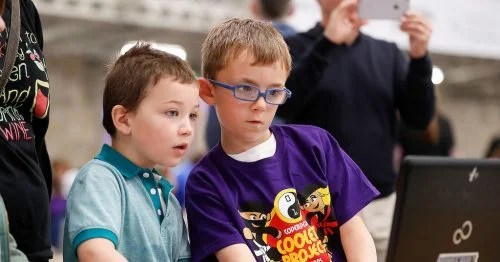 A young boy in a CoderDojo Ninja T-shirt shows another young boy his project, both concentrating intently