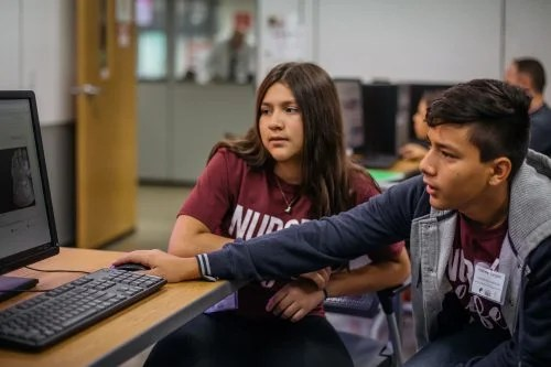 two young people coding at a computer