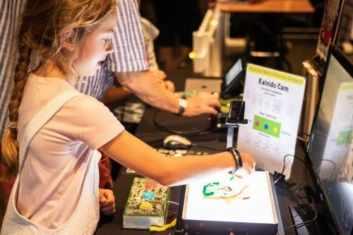 A young girl tries out a digital project at the Raspberry Pi event, Raspberry Fields 2018