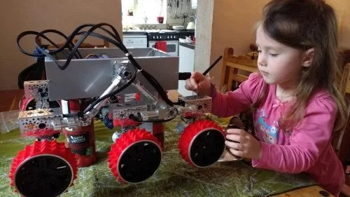 A young girl inspects the Yuri 3 Mars rover