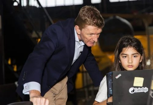 Tim Peake observes a girl writing code that will run in space