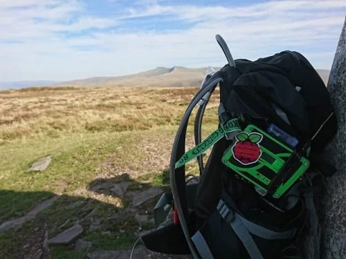 A green 3D-printed case with a Raspberry Pi sticker on it, on a black backpack leaning against a cairn. In the background are a sunny mountain top, distant peaks, and a blue sky with white clouds.