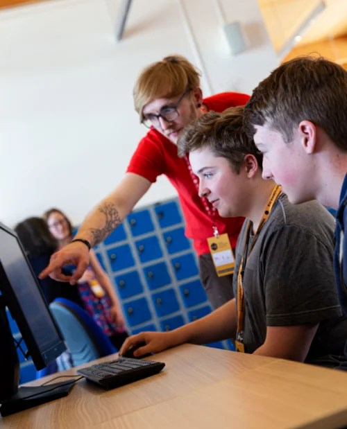Male teacher and male students at a computer