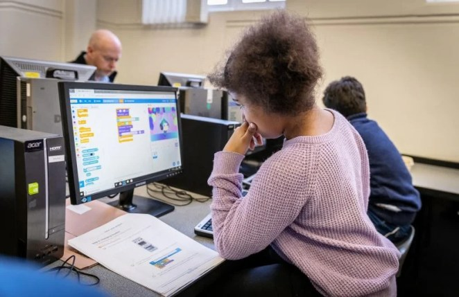 A girl doing Scratch coding in a Code Club classroom
