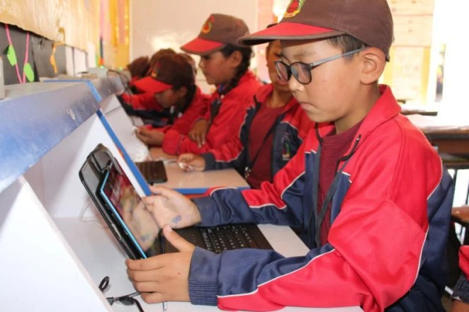Young learners in red jackets and baseball caps using tablets to learn in a Himalayan school