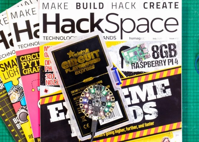 Hackspace magazines fanned out with adafruit gift on top