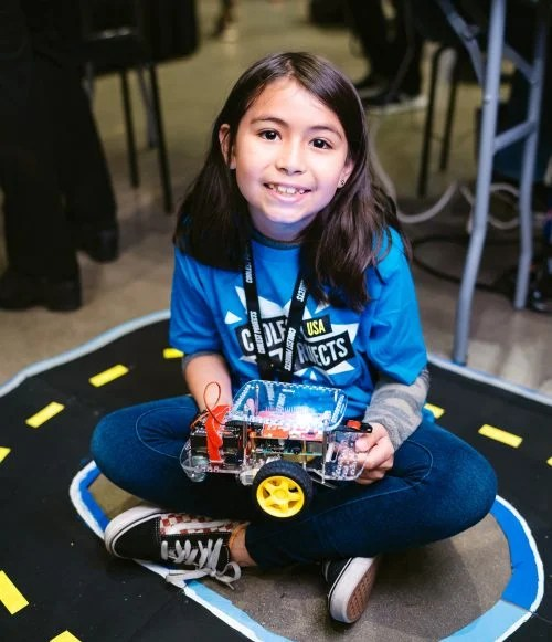 A smiling girl holding a robot buggy in her lap