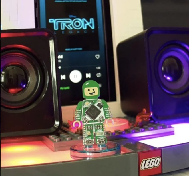 A Tron mini figure on the reader with the Tron movie soundtrack seen playing on the screen behind it