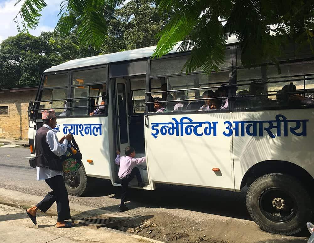 kid runs to catch school bus in Pokhara Nepal