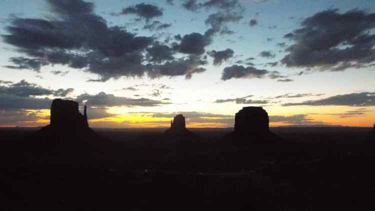 The sun setting over the monument valley butes