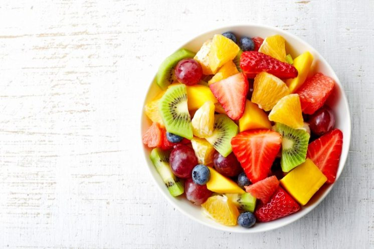healthy bowl of cut fruit on white surface