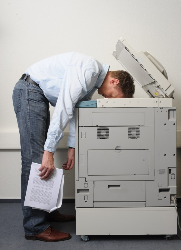 Male tired at work, head on photocopier