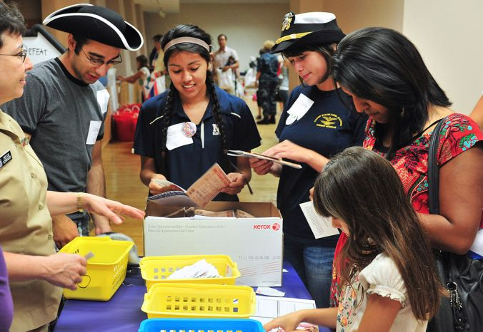 Interns from the National Museum of the United States Navy work together creating small history books for children