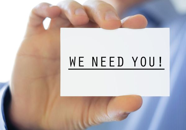 A hand holds up a business card with the words 'WE NEED YOU' written on it