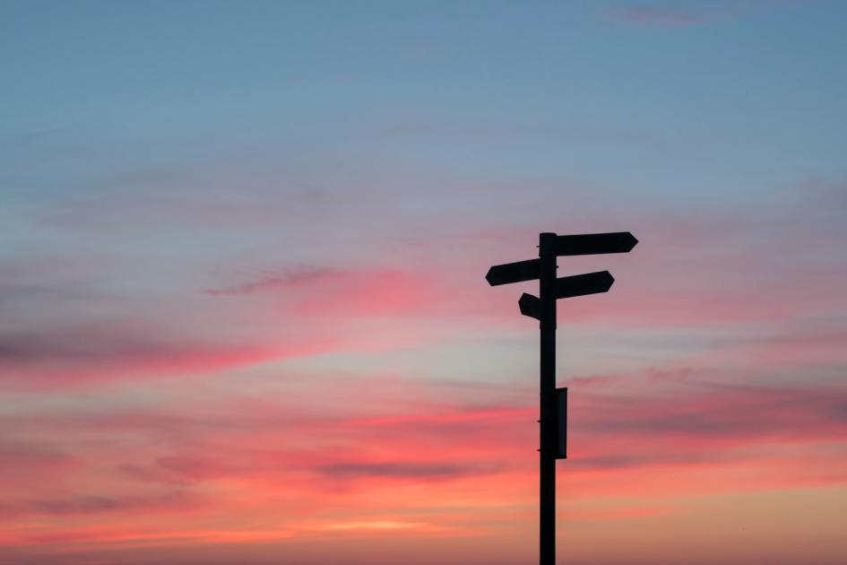 a multi-directional sign against a sunset