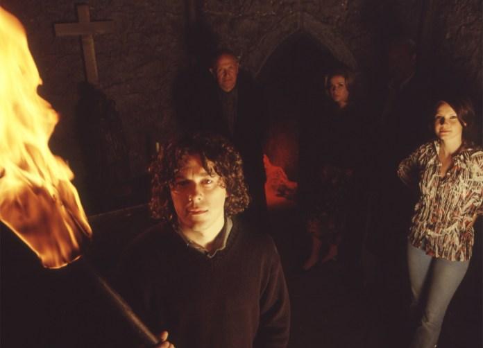 Alan Davies (Jonathan Creek), Steven Berkoff (Herman), Julia Sawalha (Carla), and Lisa Stokke (Jodee) explore Satan's Chimney (c) BBC Studios