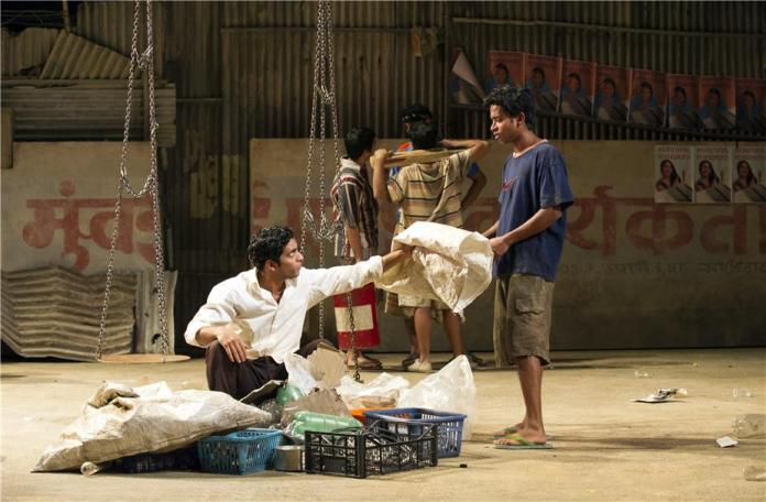 Shane Zaza (left) as Abdul In Behind the Beautiful Forvers at the National Theatre (x) National Theatre
