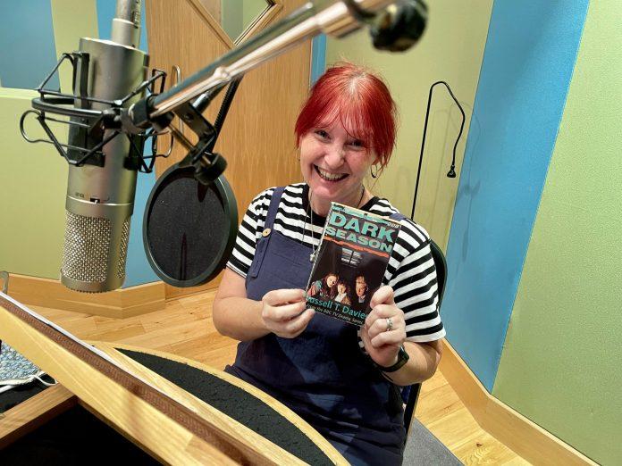 Victoria Lambert (Marcie) with a copy of Davies' original novelisation at the recording of the audiobook (c) Big Finish Dark Season Russell T Davies