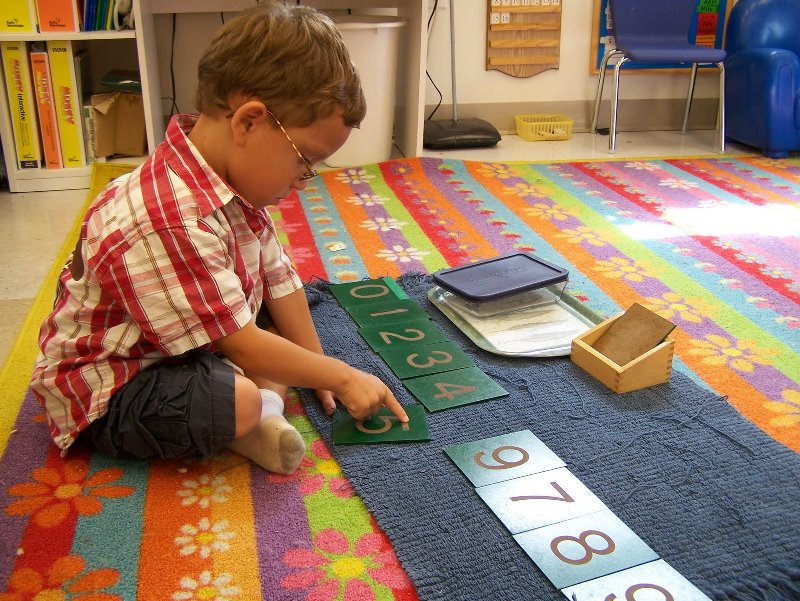 child tracing on sandpaper numbers