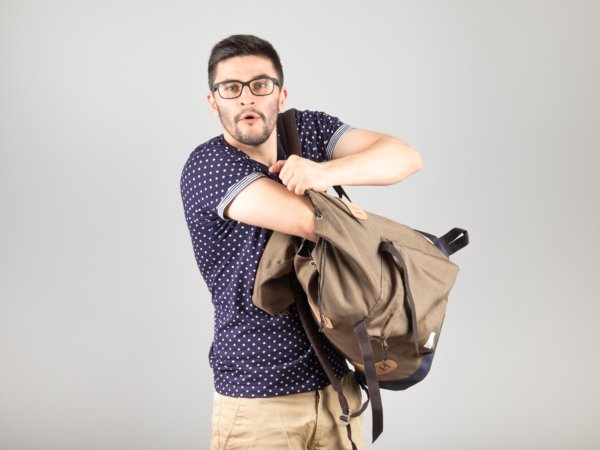 Man standing and getting something out of his backpack isolated on gray