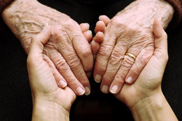 Hände einer jungen und einer alten Person ineinander
