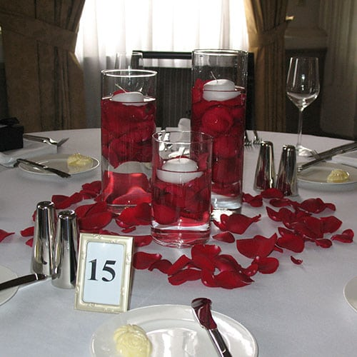 Trio of cylinders with rose petals inside and outside vases
