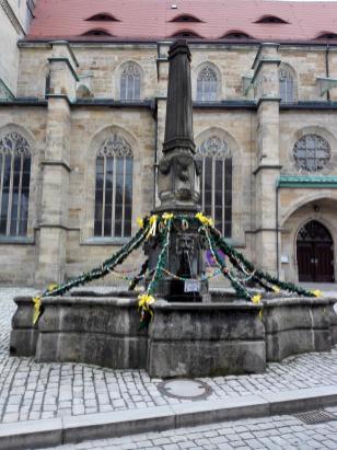Österlich geschmückter Brunnen neben der Stadtkirche