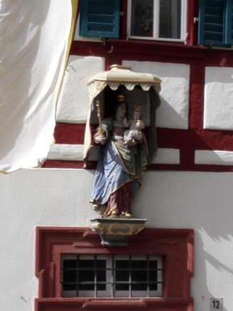 Heiligenskulptur an einem Wohnhaus neben der Stadtkirche