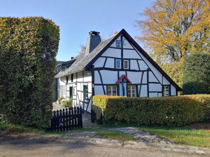 Denkmalgeschütztes Haus in Eicherscheid. Typisch für die Region sind die haushohen Buchenhecken und das Kreuz an der Hausfassade