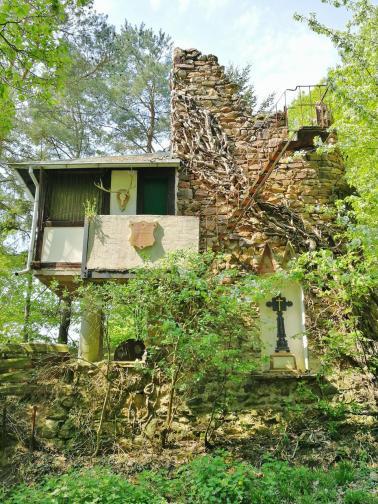 Skurriler, halb verfallener Turm mit angebauter Jagdhütte am Waldrand