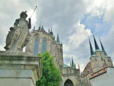 Skulptur auf dem Domplatz vor dem Dom (links) und der St. Serveri Kirche (rechts)