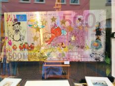 Gemälde im Schaufenster einer Galerie. Ein 500 Euro-Schein zum Preis von 3.400 Euro. Ob das ein gutes Geschäft ist?