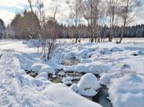 Kleine Wasserläufe im Venn reißen Lücken in den Schnee