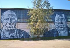 Arbeiterportraits an einer Hallenwand auf dem Gelände