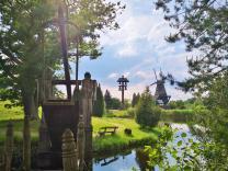 Klappbrücke über den Wassergraben, dahinter das Haus am Dorfplatz mit dem Nachbau der Mühle Sanssouci