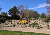 Stadtwappen im Park am Gondelweiher, dahinter die Burg