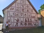 Symbole städtischen Lebens auf einem Haus bei der Marienkirche