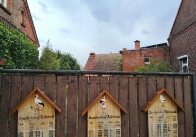 Tafeln an den Häusern informieren über den Bruterfolg in den jeweiligen Nestern
