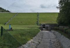 Die Rückseite der begrünten Staumauer mit dem Abfluss der Weißen Göltzsch
