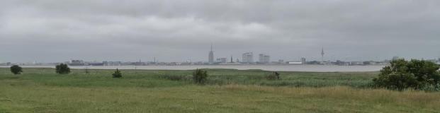 Blick über den Deich und die Weser auf die Skyline von Bremerhaven