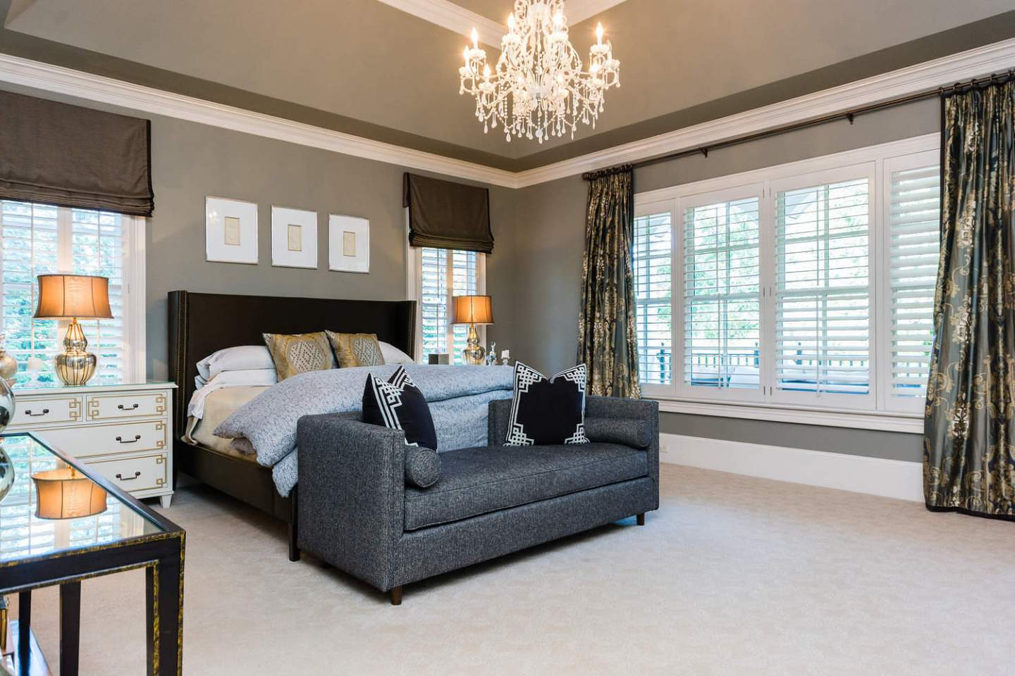 Gray Master Bedroom. How to decorate your house in gray. White chandelier and gray bench in front of Brown Silk bed.
