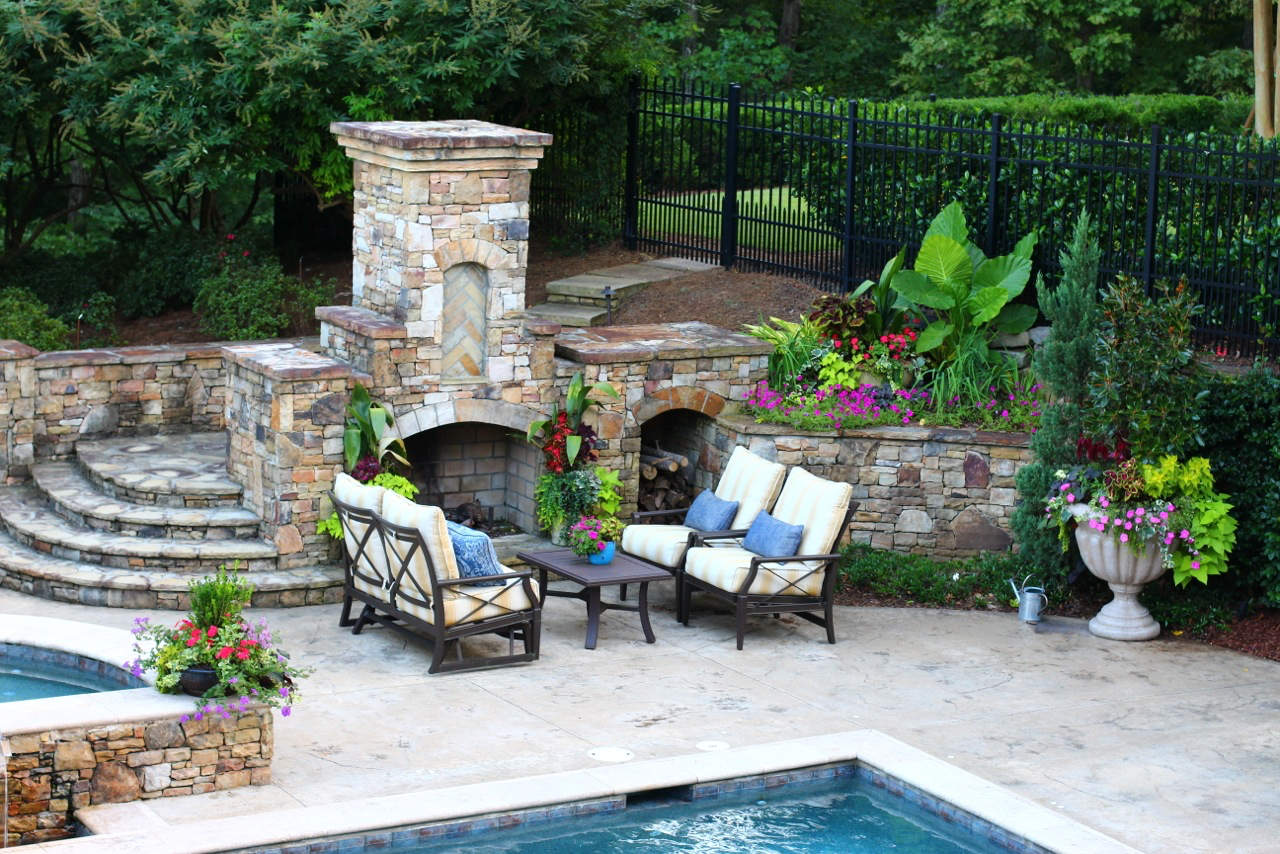 Yellow stripe outdoor furniture cushions. Outdoor furniture by stone fireplace.