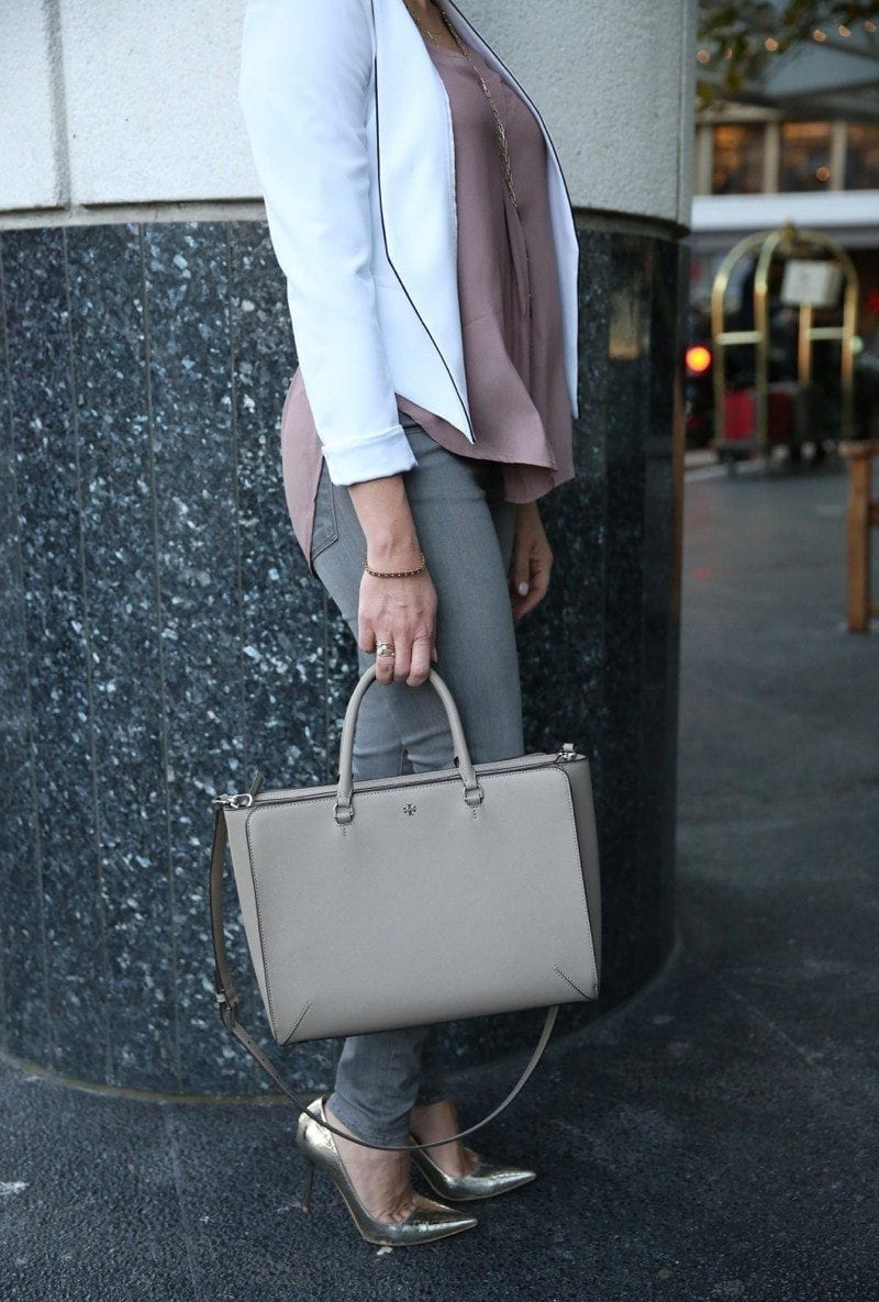 Tory Burch Handbag and gray jeans with gold pumps.