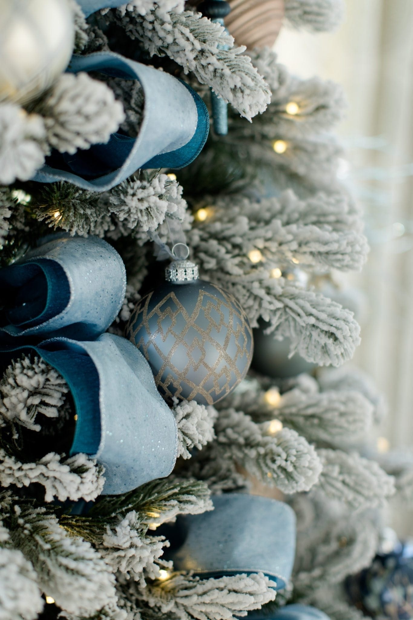 Peacock blue and dark blue layered ribbon on pre lit flocked white Christmas tree.