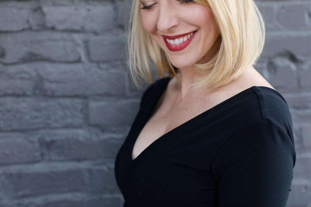 black v neck alice and olivia black bodysuit on blonde girl with red nars lipstick