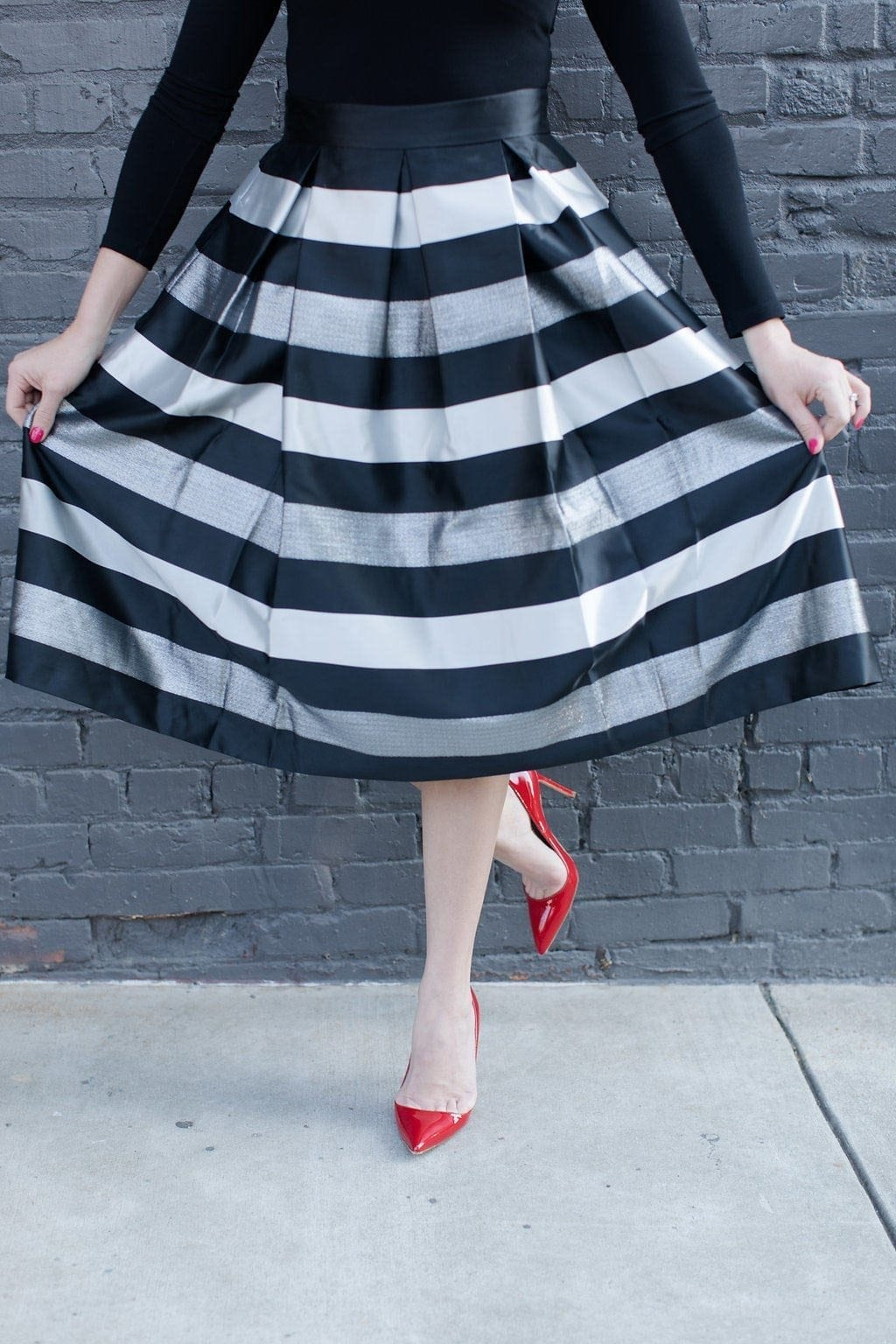 ladylike holiday looks in full skirt in black and silver with red patent leather shoes against gray brick wall